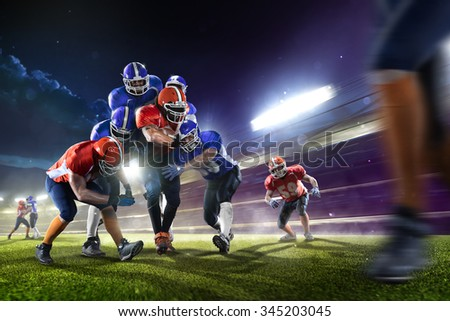 american football players in the action in grand arena - stock photo