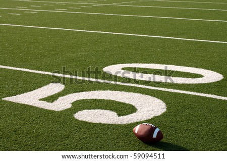 American football sitting on field next to 50 yard line. - stock photo
