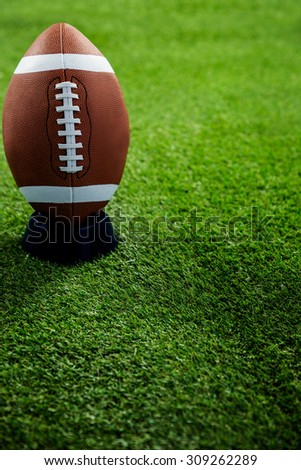 American football standing on holder on american football field