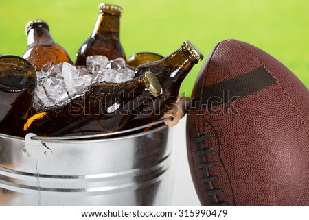 American football with a cold beer in a bucket - stock photo