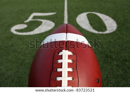 American Football with the Fifty Yard Line Marker Beyond - stock photo