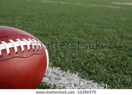 American Football with the Football Field Beyond - stock photo