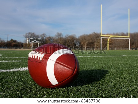 American Football with the goal posts beyond - stock photo