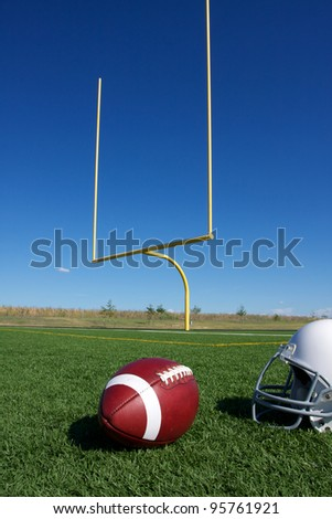 American Football with the goal posts or uprights in the background - stock photo