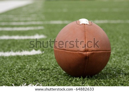 American Football with yard lines beyond - stock photo