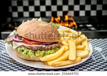 American hamburger with French fries in flames - stock photo