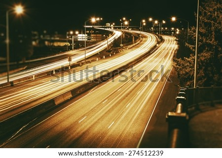 American Highways System at Night. Traffic in Motion. Long Exposure Photo. Dark Sepia Color Grading. - stock photo