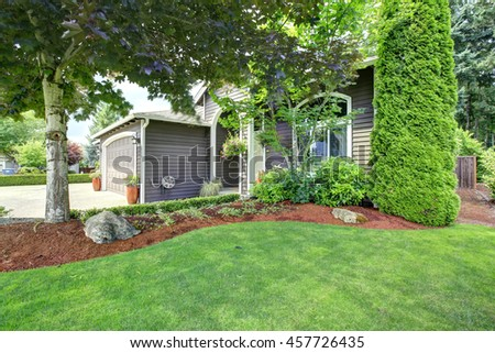 American house with landscape design. View of entrance porch and garage