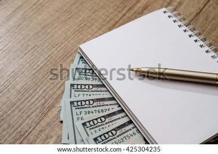 american hundred dollar and pen and empty note on desk