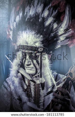 American Indian warrior, chief of the tribe. man with feather headdress and tomahawk - stock photo