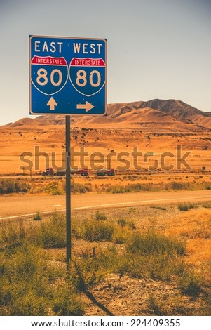 American Interstate I-80 in Nevada State. Interstate Entrance Sign and Some Speeding Semi Truck. - stock photo