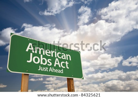 American Jobs Act Green Road Sign Against Dramatic Sky, Clouds and Sunburst.