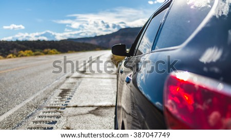 American landscape long endless asphalt north american mountain road with car rear close up journey in beautiful sunny autumn weather somewhere in the USA - stock photo