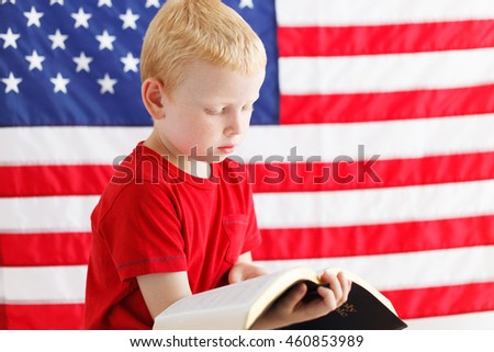 American little boy reading Holy Bible . American flag on a background