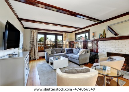 American luxurious living room interior in grey and brown tones. Furnished with Large corner sofa, vintage cabinets and coffee table. White ceiling with brown wooden beams. Northwest, USA