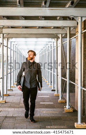 American man with beard, mustache traveling in New York, dressing in black, shirt, pants, shoes, carrying leather bag, holding laptop computer, walking on sidewalk bridge. Man casual street fashion. - stock photo
