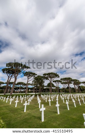 American military cemetery with white crosses in a meadow of green grass in Nettuno in Italy - stock photo