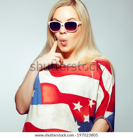 American Mom Concept: Surprised young pregnant woman in american flag like dress and trendy sunglasses posing over light blue background. Stars and stripes. Hipster, pop-art style. Studio shot
