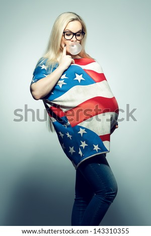 American Mom Concept: Young pregnant woman in american flag like dress and trendy glasses chewing bubble gum and looking at her belly over gray background. Hipster style. Studio shot - stock photo