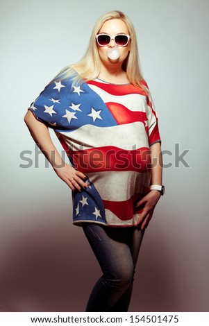 American Mom Concept: Young pregnant woman in american flag like dress and trendy sunglasses chewing bubble gum and posing over gray background. Hipster style. Studio shot - stock photo