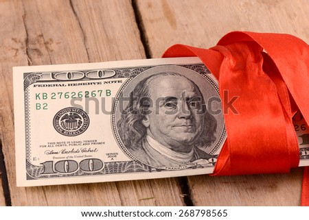 american money dollars and red ribbon on wooden plate, business concept - stock photo