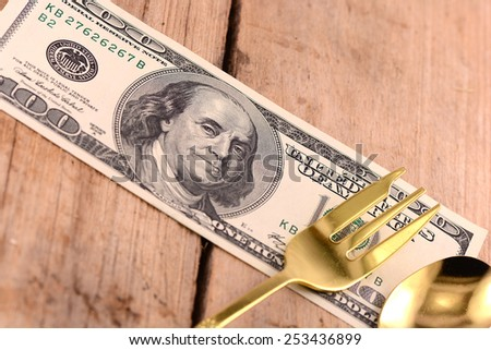 american money dollars and spoon on wooden plate - stock photo
