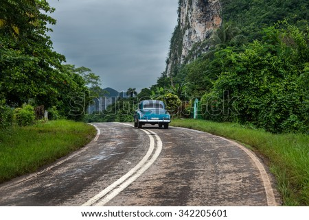 American oldtimer drive lonely on Cuban road - stock photo