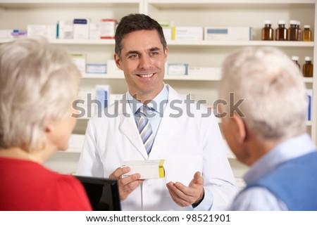 American pharmacist with senior couple in pharmacy - stock photo