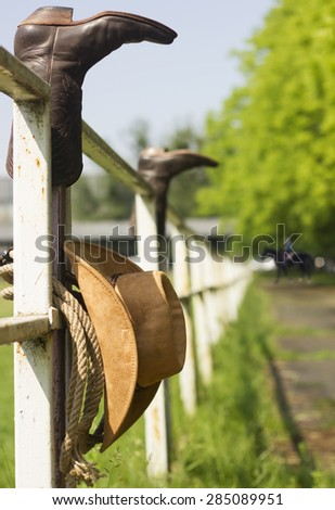American Ranch with cowboy clothes on fence - stock photo