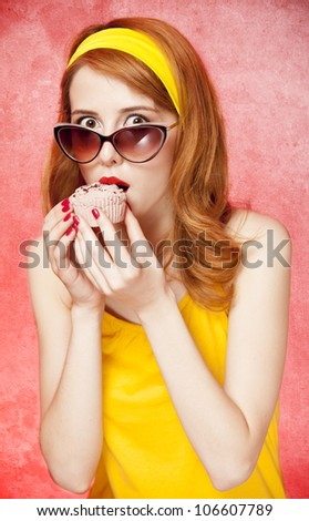 American redhead girl in sunglasses with cake. Photo in 60s style. - stock photo