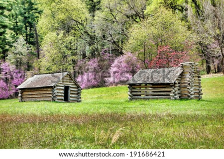 American Revolutionary War soldier housing log wood cabins on hill at Valley Forge National Historical Park military encampment of the Continental Army in the spring near Philadelphia in Pennsylvania - stock photo