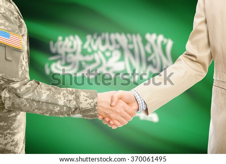 American soldier in uniform and civil man in suit shaking hands with national flag on background - Saudi Arabia - stock photo