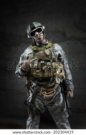 American Soldier in victory gesture on dark background - stock photo