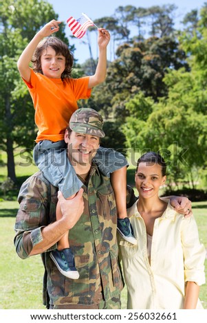 American soldier reunited with family on a sunny day - stock photo