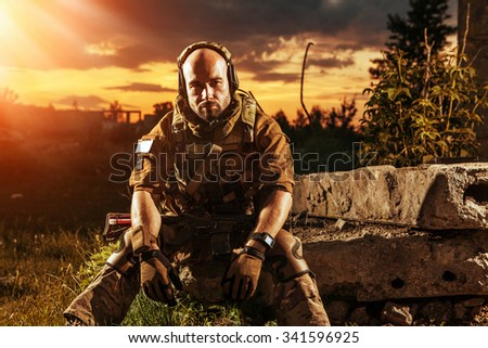 American soldier with the M4 rifle is having a rest. Sunset on the background. - stock photo