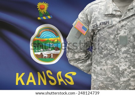 American soldier with US state flag on background - Kansas - stock photo