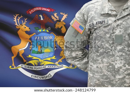 American soldier with US state flag on background - Michigan - stock photo