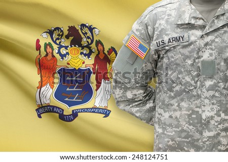 American soldier with US state flag on background - New Jersey - stock photo