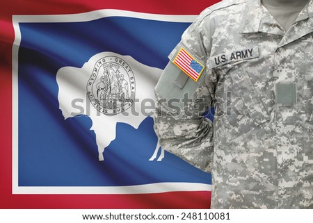 American soldier with US state flag on background - Wyoming - stock photo