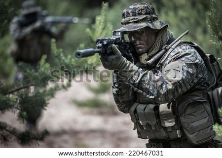 American soldiers during patrol, dressed in tiger stripe camouflage - stock photo
