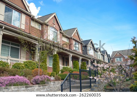 American street with townhouses with nice landscaping under blue sky - stock photo