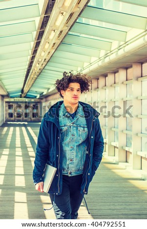 American student studying in New York. Wearing blue jacket with hood, holding laptop computer, guy with freckle face, curly long hair, walking on indoor walkway with glass wall, celling, wooden floor. - stock photo