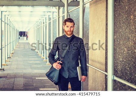 American student with beard, mustache traveling in New York, wearing black shirt, shoulder carrying leather bag, holding laptop computer, walking on sidewalk bridge. Instagram filtered effect.  - stock photo