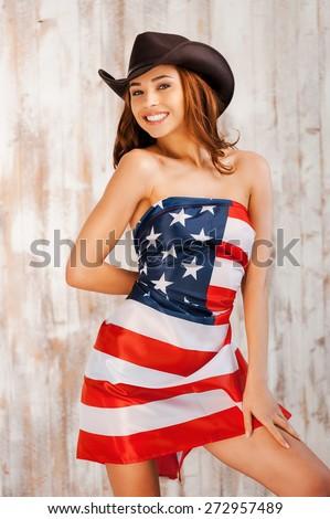 American style. Beautiful young shirtless cowgirl wearing hat andcovering herself by American flag while standing against the wooden background  - stock photo