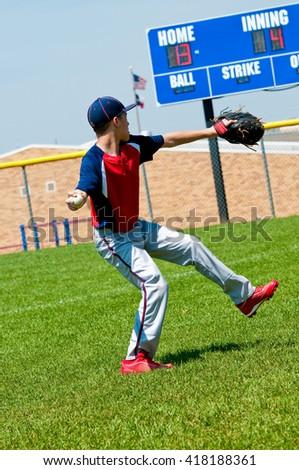 American teenage baseball boy pitching with scoreboard in background. - stock photo