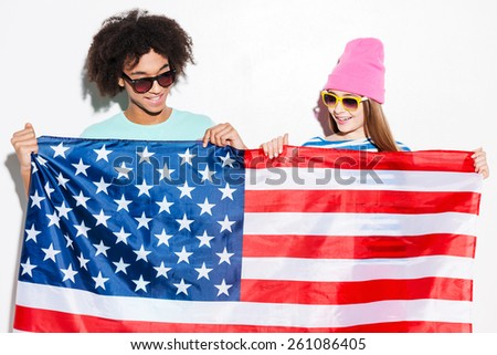 American teens. Funky young couple holding American flag in front of them and smiling while standing against white background - stock photo
