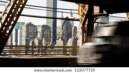 American Truck speeding on the Queens bridge, New York Downtown in the background - stock photo