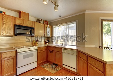 American typical kitchen interior with white appliances, wood cabinets and hardwood floors.