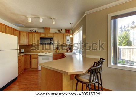 American typical kitchen interior with white appliances, wood cabinets and hardwood floors.  - stock photo