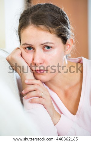 American upset woman sitting in domestic interior with headache